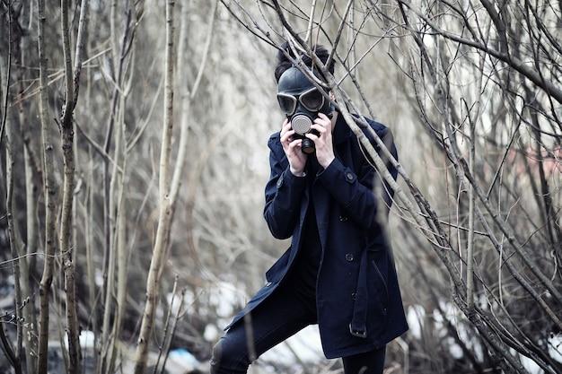 Парень в пальто и противогазе. постапокалиптический портрет азиатки в маске от радиации. мальчик кореец в маске от отравления газами. постъядерная маска на азиатском.