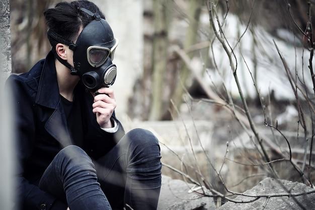 コートと防毒マスクの男。ポスト黙示録的な肖像画アジア人は放射線からマスクされています。その少年はガス中毒のマスクをした韓国人です。アジアのポスト核マスク。