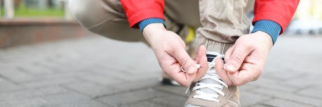 ジャケットの男はブーツに靴ひもを結ぶ