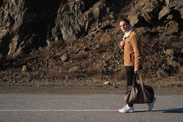 산에 있는 남자가 가방을 들고 걷는다