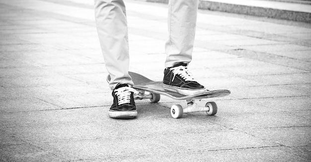 운동화를 신은 남자는 스케이트보드에 발을 올려놓고 신호가 시작되기를 기다립니다