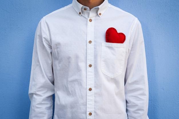 Парень в белой рубашке с красной валентинкой в кармане