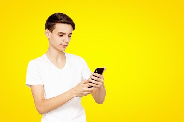 노란색 배경에 전화 흰색 티셔츠에 남자. 현대 기술의 개념, 소셜 네트워크에 처방 된 어린 십대