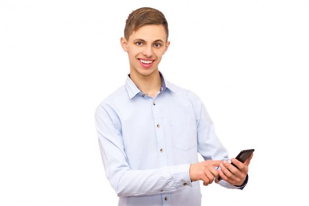 흰색 티셔츠를 입은 남자가 전화로 작동합니다.