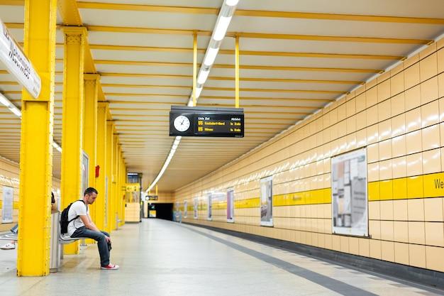 Парень один ждет поезд на станции метро.