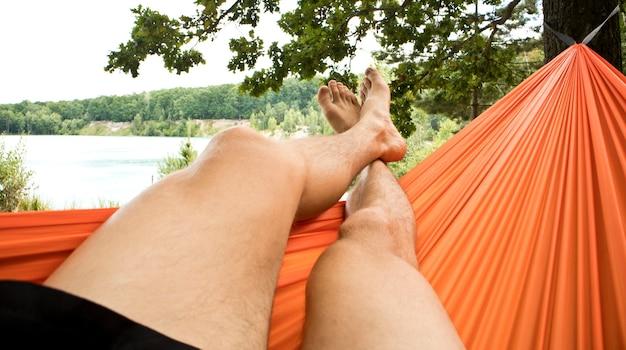 남자는 해먹에서 차갑고 휴식을 취하고 푸른 호수를보고 있습니다.