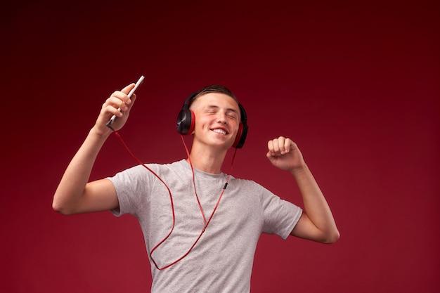 Парень танцует в наушниках. подросток слушает треки и танцует под ритм музыки.