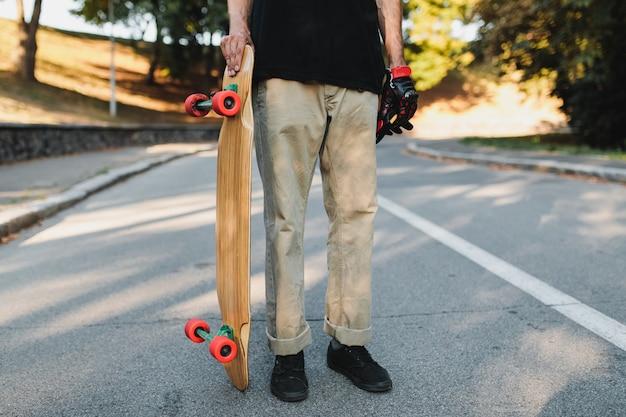 男は赤い車輪の付いたボードを持っています。永遠の都でのスケートボード。高品質の写真