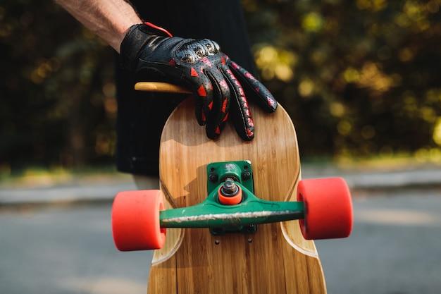 Парень держит доску с красными колесами. скейтбординг в вечном городе. фото высокого качества