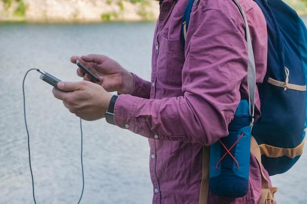 그 남자는 스마트폰을 손에 들고 휴대용 충전기를 들고 있다. 녹지와 호수가 있는 자연의 배경에 있는 남자.