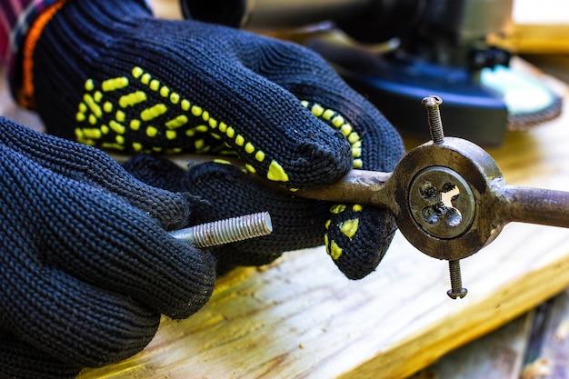 남자는 나사산 볼트 자물쇠 제조공 워크숍을 위해 탭을 잡고 있습니다.