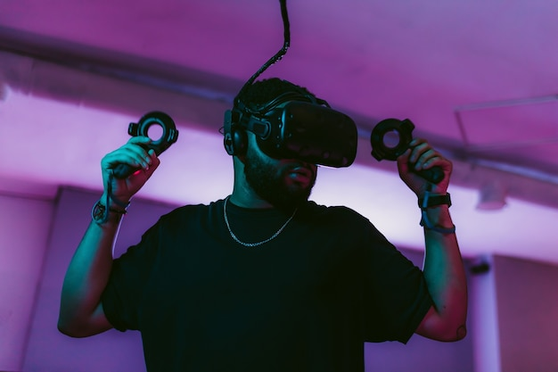 남자는 게임 네온 룸에서 온라인 슈팅 게임을하고 있습니다