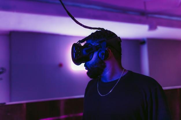 男はゲームネオンルームでオンラインシューターをプレイしています