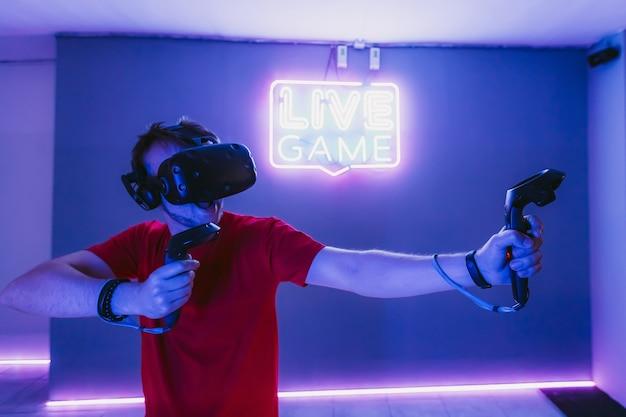 Парень играет в онлайн-шутер в игровой неоновой комнате