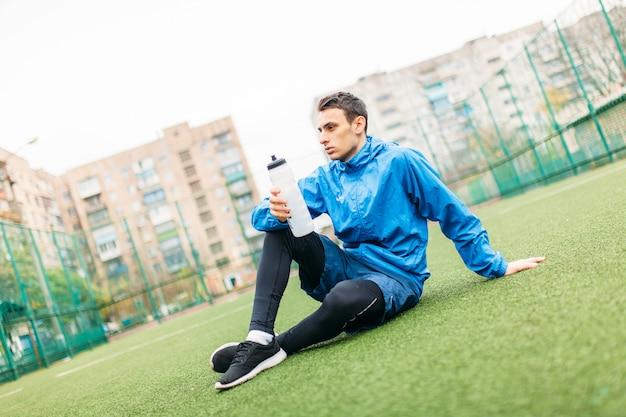 男は良い運動の後に休んでいます。運動後の男、サッカー場の飲料水。スポーツウェアの美しい男の肖像画。
