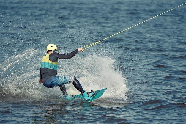 남자는 강에서 웨이크 보드를 타고있다. 활동적이고 익스트림 스포츠.