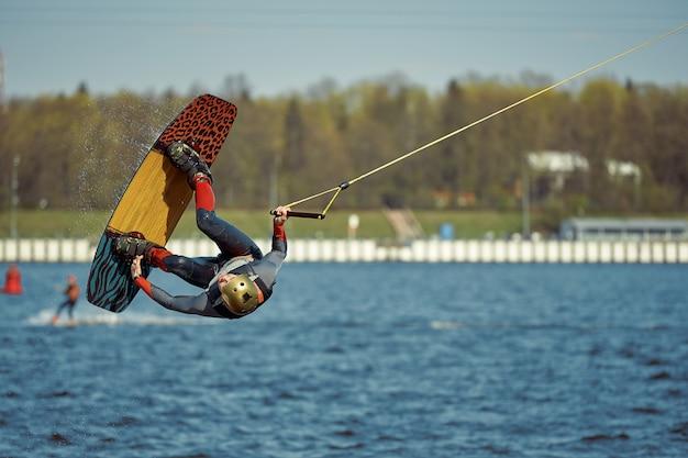 Парень катается на вейкборде по реке. активные и экстремальные виды спорта.