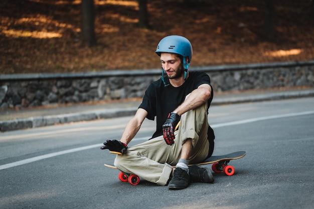 男は丸太盤に座っています。スケートボードの後に休んでください。高品質の写真