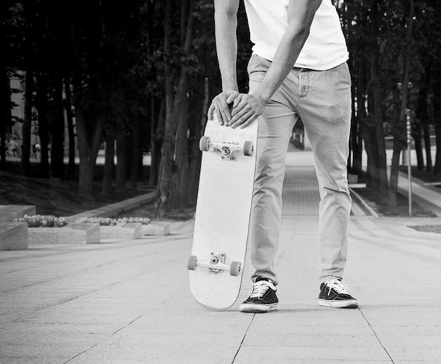 그 남자는 태양 아래 공원에 서서 스케이트보드에 기대어 있다