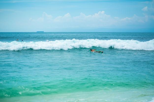 男は海のサーフボードで泳いでいます。夏休みの健康的なアクティブライフスタイル。