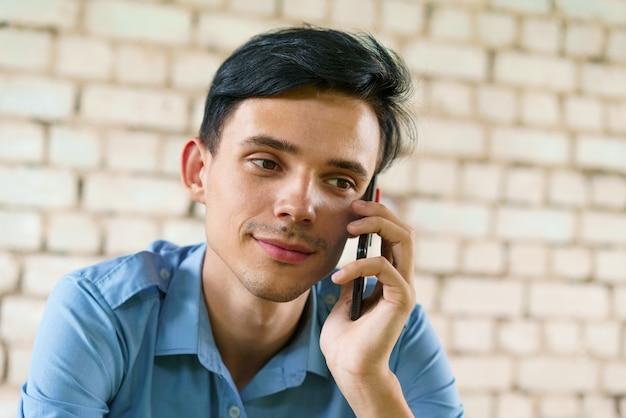남자는 흰색 벽돌 벽 배경에 전화 근접 촬영 백인 젊은 갈색 머리 남자에 대 한 얘기입니다 ...