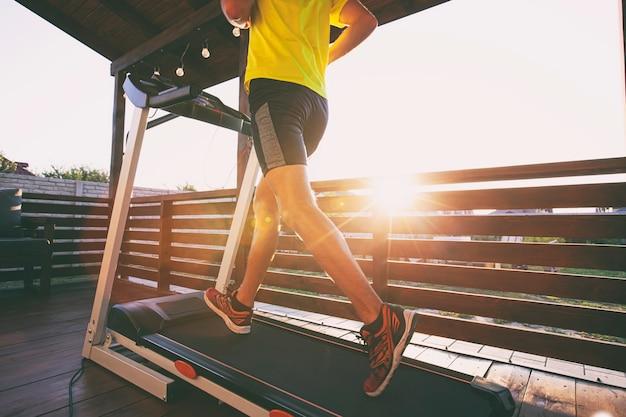 彼の家のテラスでトレッドミルでジョギングしている男。社会的孤立または検疫の概念