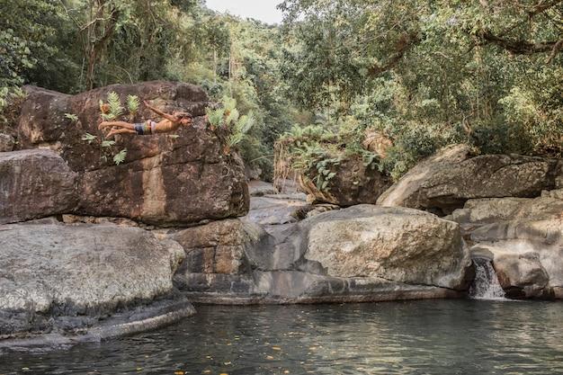 Парень прыгает с камня в воду