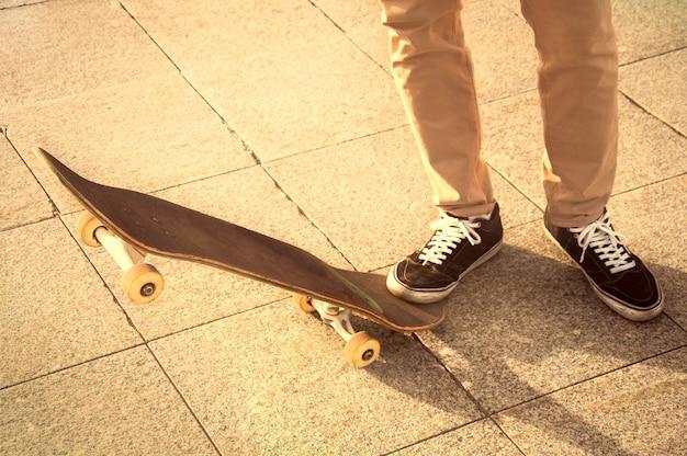 그 남자는 스케이트보드를 들고 지는 태양 광선 아래 공원에 서 있었다