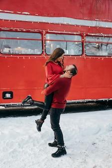 Парень поднял девушку на руки и кружит по ней на фоне красного автобуса. фото высокого качества