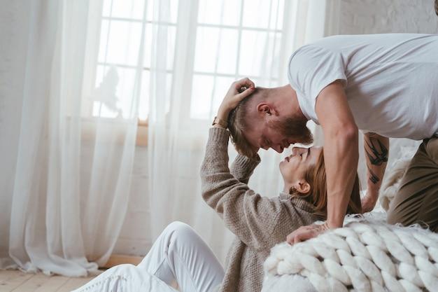 Парень на кровати целует девушку, которая сидит на полу