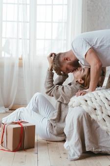 Парень на кровати целует женщину, которая сидит на полу