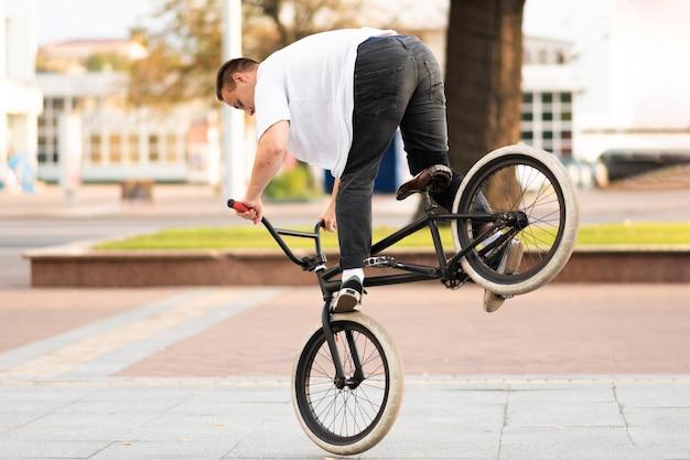 Парень на велосипеде bmx делает трюк на переднем колесе. для любых целей.