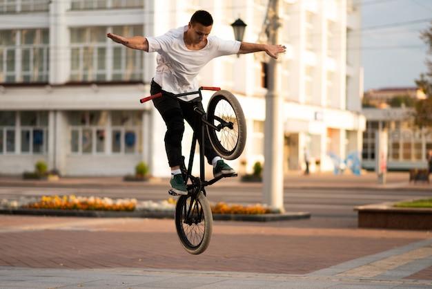 Парень на велосипеде bmx отпускает руки в прыжке. для любых целей.