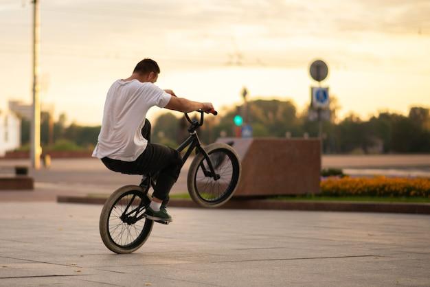 Парень на велосипеде bmx едет на заднем колесе. для любых целей.