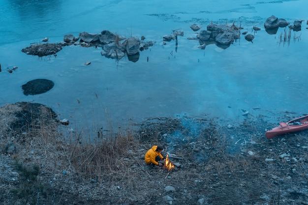 Парень на озере разводит огонь