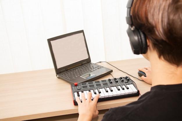 신디사이저의 남자가 집에서 음악을 씁니다.