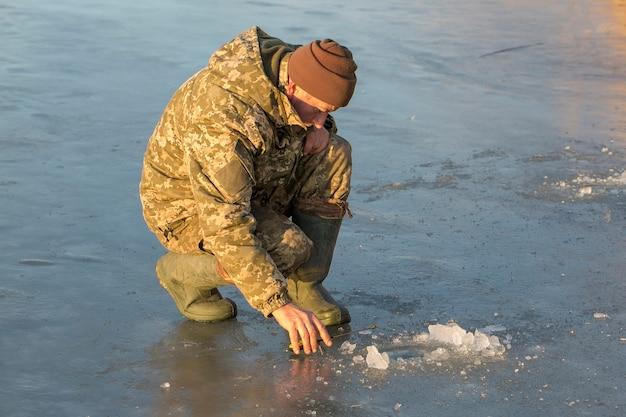 구멍에서 낚시하는 겨울에 남자는 작은 낚싯대를 잡는다