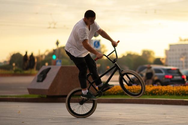 Парень выполняет трюк bmx, стоя на заднем колесе. для любых целей.
