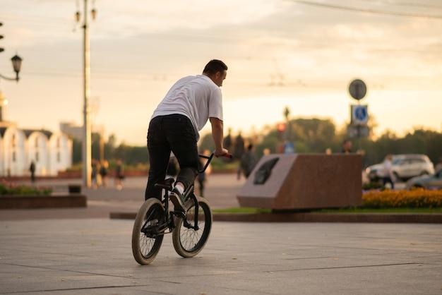 Парень едет на велосипеде bmx по улице. для любых целей.