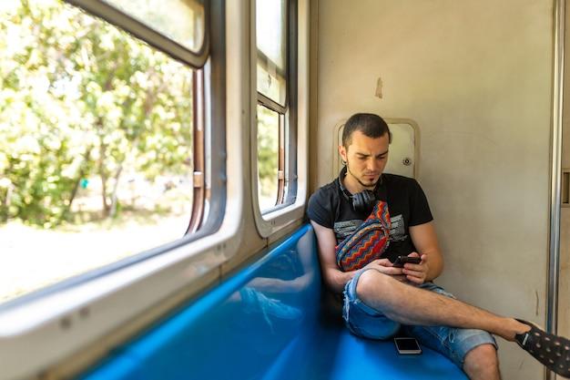 그 남자는 기차 차의 창문 근처에 타고 있습니다. 지루한 긴 여행.