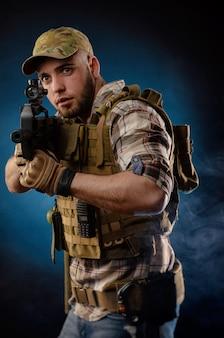 Парень военный агент в бронежилете с автоматом Premium Фотографии