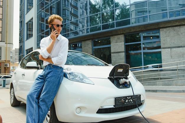 Парень сел на капот машины. его машина заряжается на зарядной станции. мужчина смотрит на экран смартфона и улыбается.