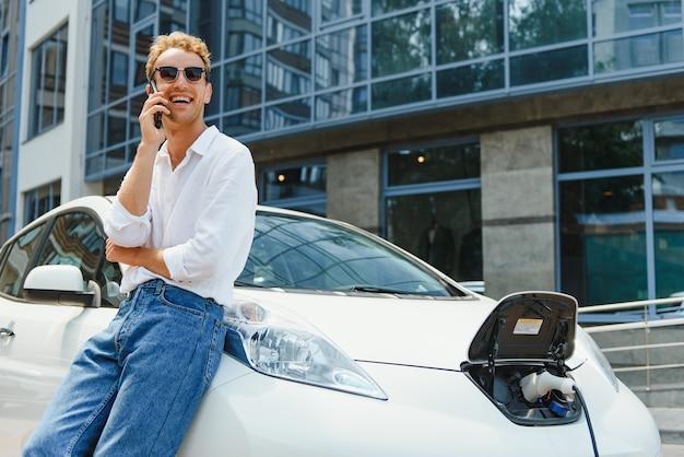 그 남자는 차의 후드에 앉았다. 그의 차는 충전소에서 충전 중입니다. 한 남자가 스마트폰 화면을 보고 미소를 짓고 있습니다.