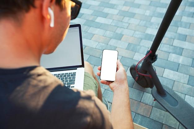電動スクーターとラップトップを持ってベンチに座って、空白の白い画面で電話を見せている男