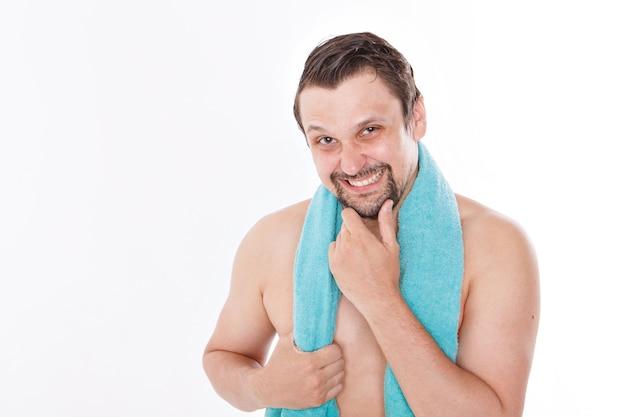 Парень гладит бороду. утренние процедуры в ванной. синее полотенце на шее. отдельный на белом фоне. копировать пространство