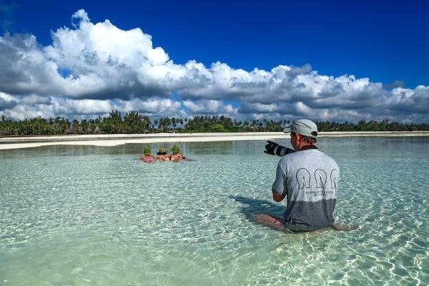 그 남자는 해변의 물에서 여자의 사진을 찍는다