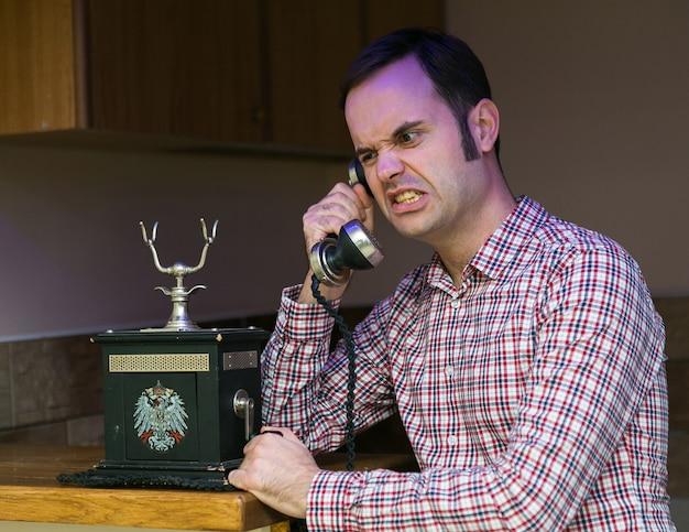 Парень разговаривает по старому телефону, деловые переговоры с покупателями