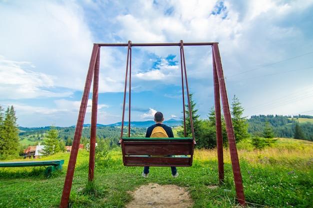 Парень-турист садится на качели и наслаждается красивым природным пейзажем летних карпат.