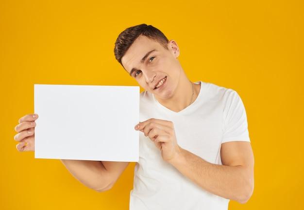 Парень с листом бумаги на желтом фоне склонил голову в сторону обрезанного вида. фото высокого качества