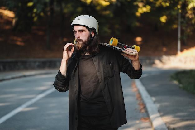ボードを持った男はタバコを吸います。ライフスタイルスタイル。高品質の写真